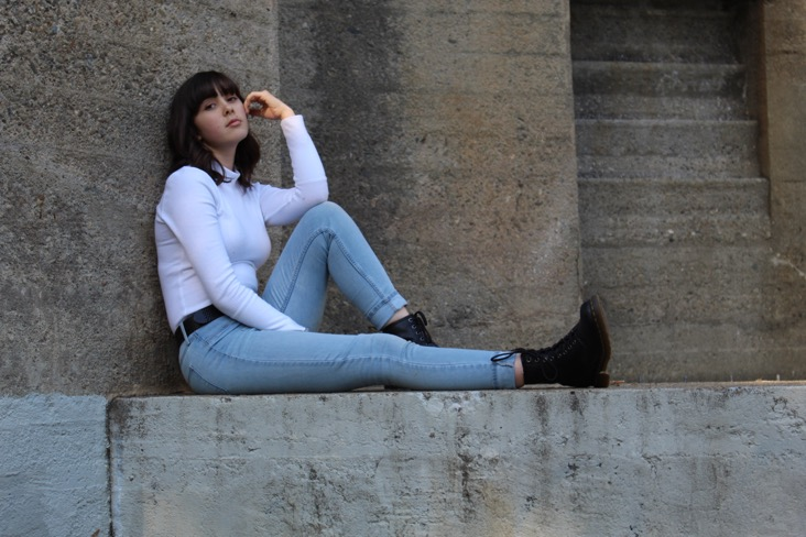 Kaia sitting on concrete structure, same image as album cover