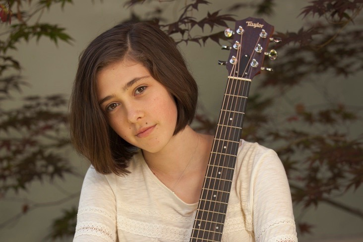 Kaia with arms wrapped around vertical guitar